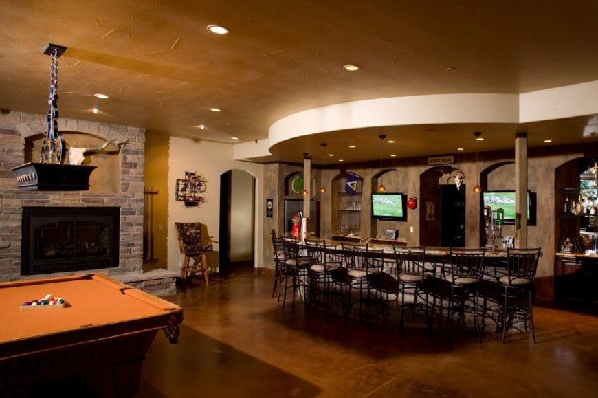 On the lower level, a cavernous room includes a game room and home bar. This room is ideal for entertaining a large amount of guests, as there is ample seating at the bar and two televisions on either side of the entrance into the wine cellar.