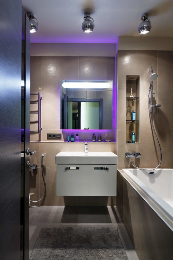 The larger of the apartment's two bathrooms features a large tile-enclosed soaking tub and a modern floating vanity. The purple lights make another appearance around the sink's mirror.