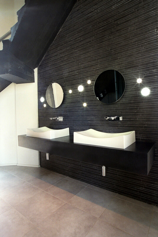 The next floor up contains the spacious bathroom, with one wall entirely in long black tiles. Bright orb lights dot the wall between the mirrors. The two matching vessel sinks curve sensually on the minimalist black vanity.