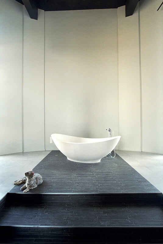 The freestanding soaking tub sits in the center of a platform in the same long, thin black tiles as on the wall behind the sinks. Steps lead up to this tub for a feeling of grandeur.