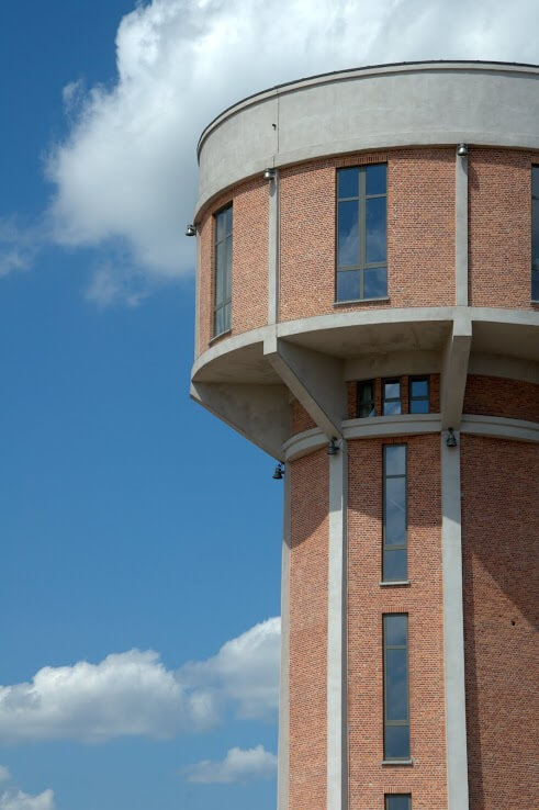 This massive brick and concrete water tower has been fitted with immense windows to provide the space with plenty of natural light. Huge windows at the top of the tower afford the top floor a magnificent view.
