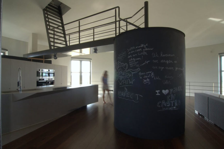 The main floor kitchen, living room, and dining areas are integrated into the rest of the building via multiple staircases. This spiral staircase in the center of the room leads up to a steel bridge and a ladder to the next floor. The staircase is enclosed in chalkboard material, which adds whimsy to this modern space.