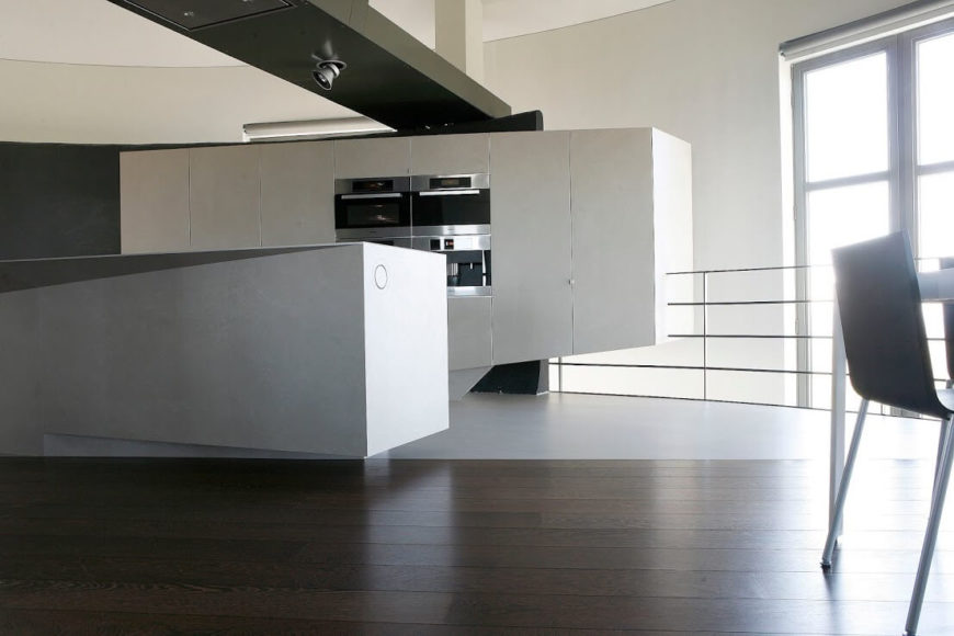 The kitchen is rimmed in a stainless steel balustrade, that when looked over, reveals the ground floor of the building. If you were to look up, you'd see the next floor.