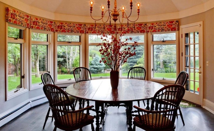 Next to the kitchen, we have a more intimate family dining space, a circular room surrounded by full height windows for an expansive garden view. The large traditional wood circular table stands beneath an old fashioned chandelier.