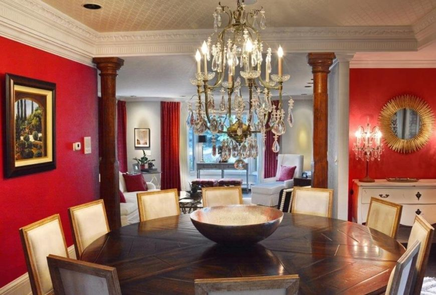 The dining room overlooks the living room, with a wide opening flanked by hardwood pillars. The massive circular table seats ten, contrasting with the bold red wall tones and opulent detail throughout the space.