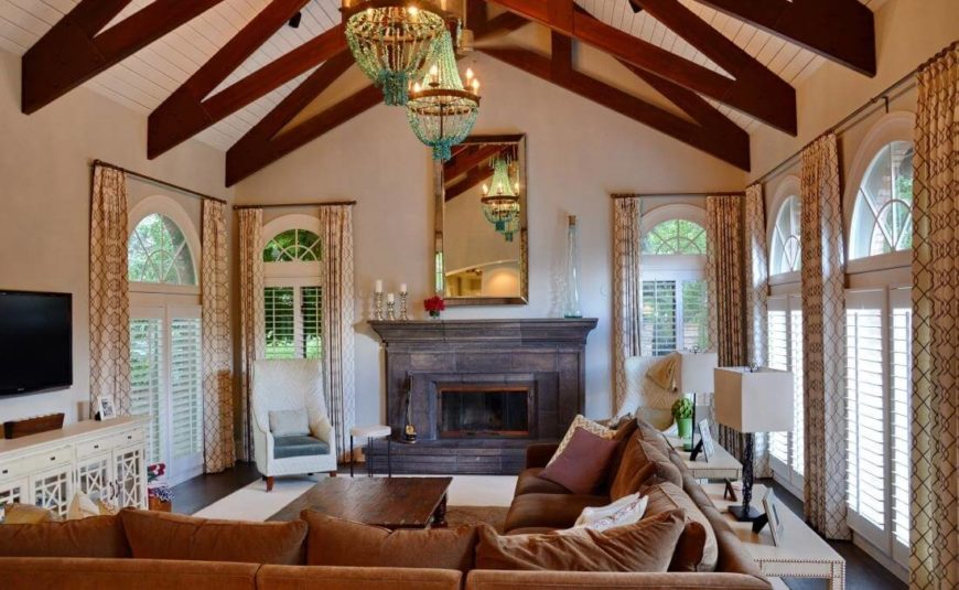 Moving into the large family room, we see a soaring vaulted ceiling with rich natural wood exposed beams hanging above a naturally sunlit space, courtesy of full height windows wrapping the room. A large L-shaped sectional dominates, with a stone fireplace in the background and white accent chairs flanking.