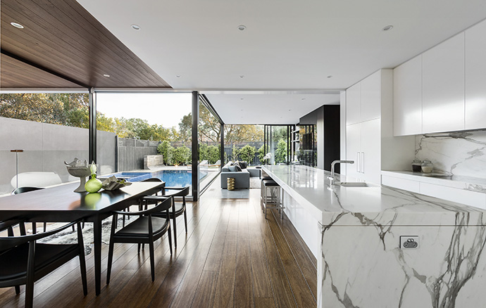 Glazing continues around the dining room and kitchen, giving the space an open and tranquil feel. White lavish marble countertops create a dazzling contrast with the dark wooden furniture of the dining room.