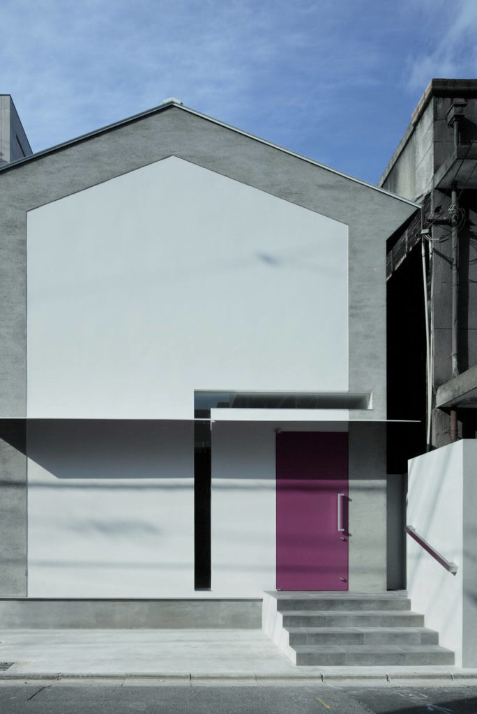 """Here's a direct view of the front facade, with simple concrete steps leading to the red front door. The L-shaped """"key"""" window wraps around the entry, bisected by the thin steel eave."""