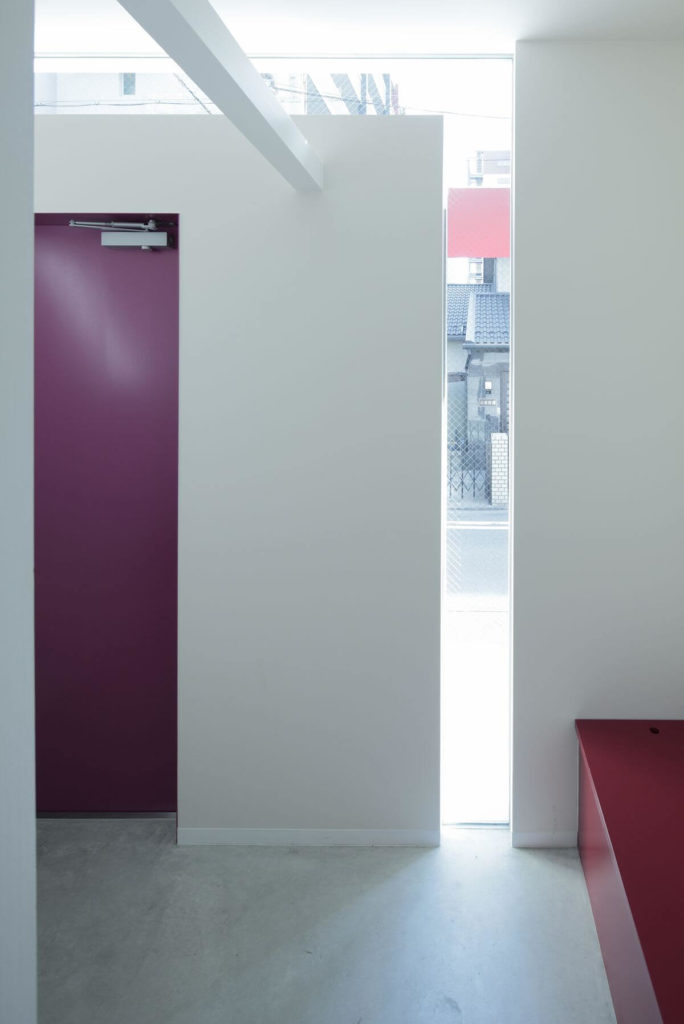 """Looking back out from just inside the front door, we see a storage bench in the foyer painted the same red wine tone as the door. A slit of light moves in from the """"key"""" window."""