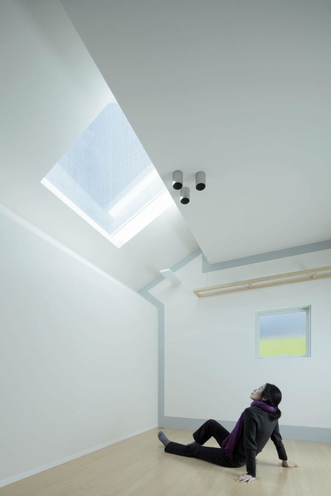 Here we see one of the residents enjoying the bright space beneath one of the skylights. The end wall is bordered in soft grey, with a light natural wood shelf built in above a window.