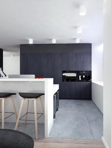 A look into the modern kitchen, which features an eat-in kitchen island and dark minimalist cabinetry.