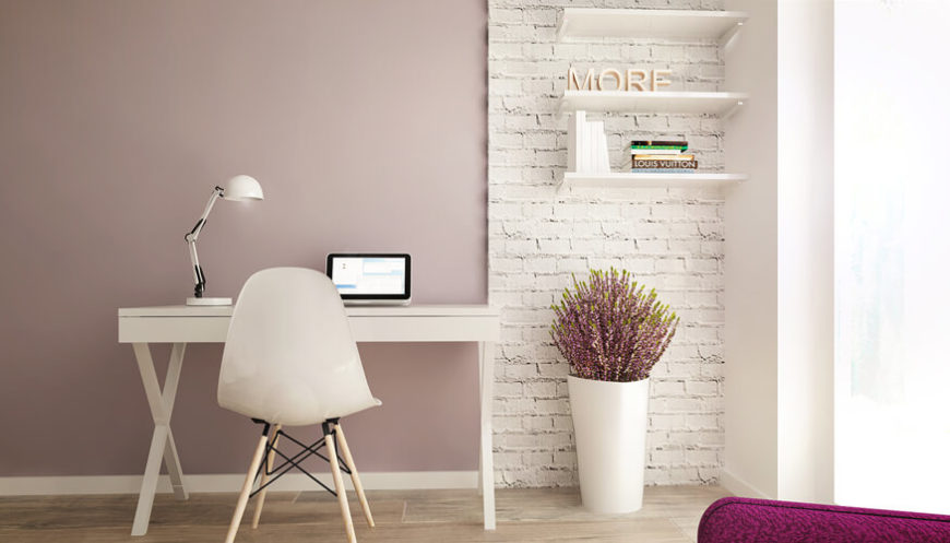 This spare, minimalist home office centers on a white writing desk in a simple X-frame, with a rustic white brick wall adding texture in the corner. Built-in shelving adorns the corner, while another appearance of light pink informs the wall.
