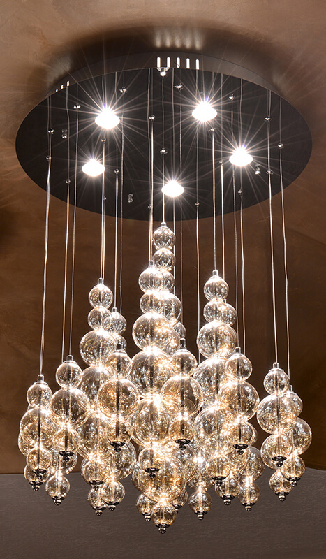 The enormous chandelier makes another bold statement in this room. While not traditional, the strings of glass bubbles glitter and cast light all around the room. The room contains three of these chandeliers to ensure maximum luxury and ample lighting.