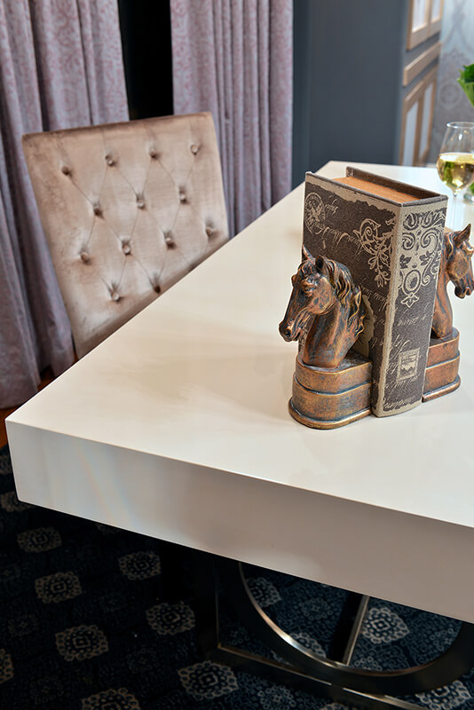 The accents on this desk are simple, yet perfectly suited. A single leather-bound book sits between two copper horse-head bookends. A glass of wine finishes out the space.