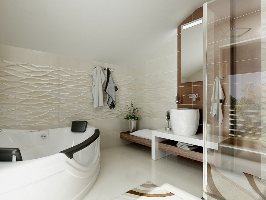 The primary bathroom continues the white theme with similar wood accents. The textured tiling on the wall is reminiscent flowing water. This bath features a large tub, walk-in shower, and cool white tiles.