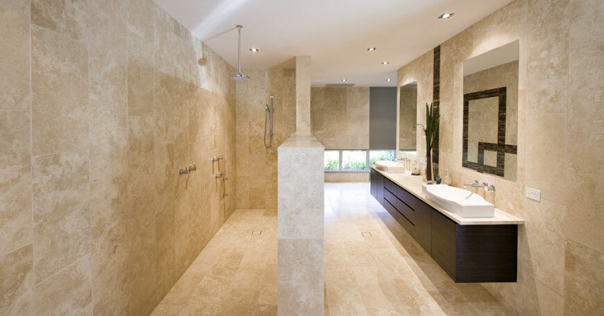 A half wall separates this large shower from the rest of the bathroom. The entire room is made of a light tan colored marble for a charming design.
