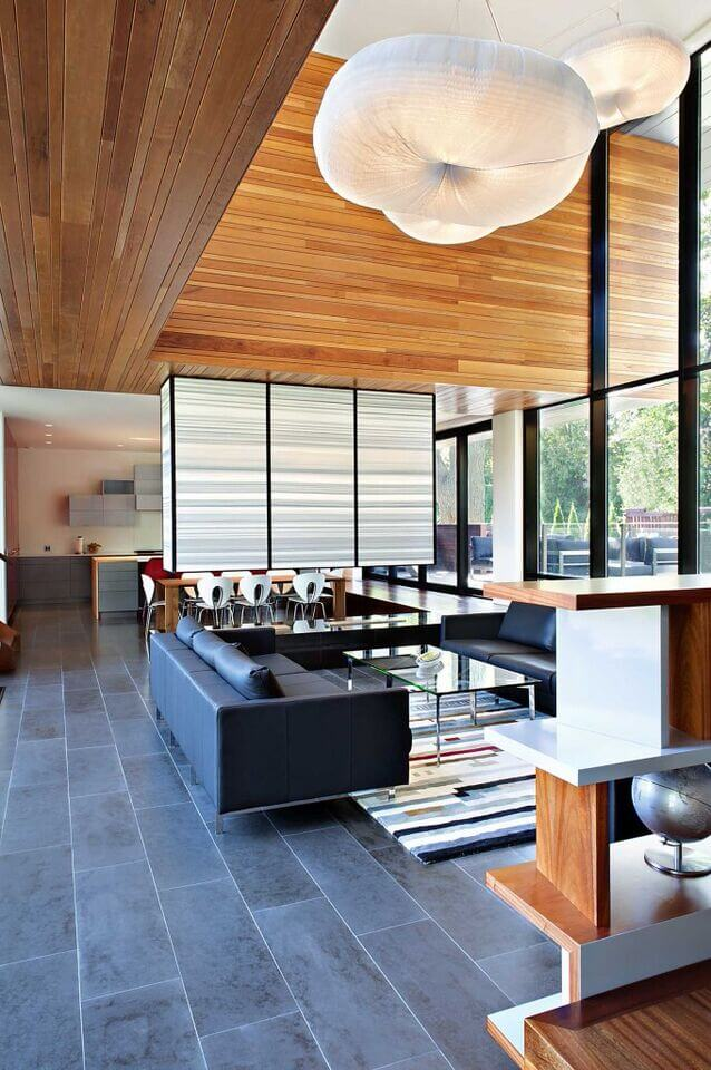 The half-wall extending from the ceiling and separating the living room from the dining room is a stunning example of an accent wall. The light colors complement the fluffy light fixtures above the seating area.