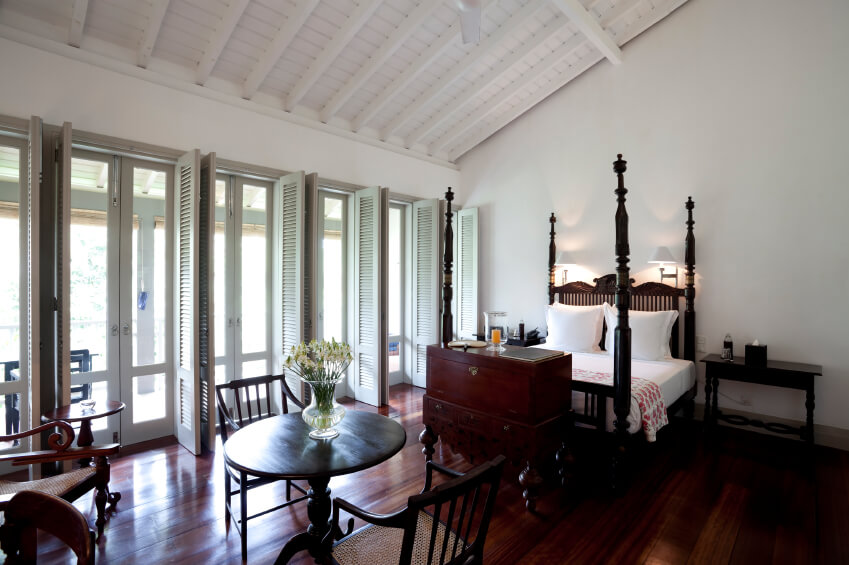 The rich, dark cherry tones of the hardwood in this bedroom offer a sense of classic elegance.  A matching chest sits at the end of an intricately carved four post bed.  A row of white shutters open to reveal a flood of natural light, while a white vaulted ceiling and eggshell walls draw your eye back to the snowy white linens atop the bed.