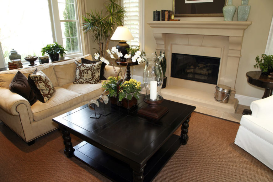 This deep, rich brown coffee table sits upon a rust colored carpet and offers sensational contrast to the furniture. A snow white armchair draws in the eye, and the same color can be seen in decorative objects and orchids on the table. Several houseplants offer a pop of green, while a cream fireplace hosts a pair of mint vases and other small decor on its mantle.