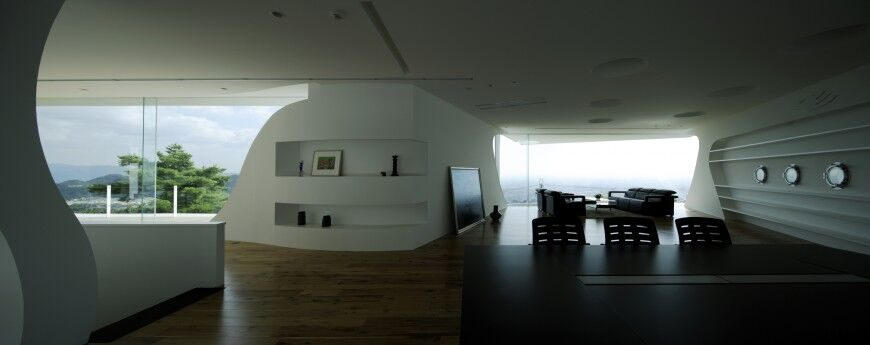 Although these walls are all the same pristine white, shelving and curved elements on one wall distinguish it from the others.