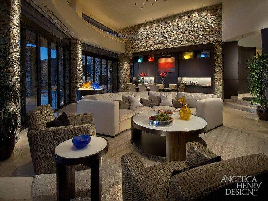 In a luxurious contemporary home, the stone walls are interrupted by a large wall with a built-in dark wood bar. The simple design of the bar also conceals lighted display cases and a beautiful painting that would be lost on the textured stone walls.
