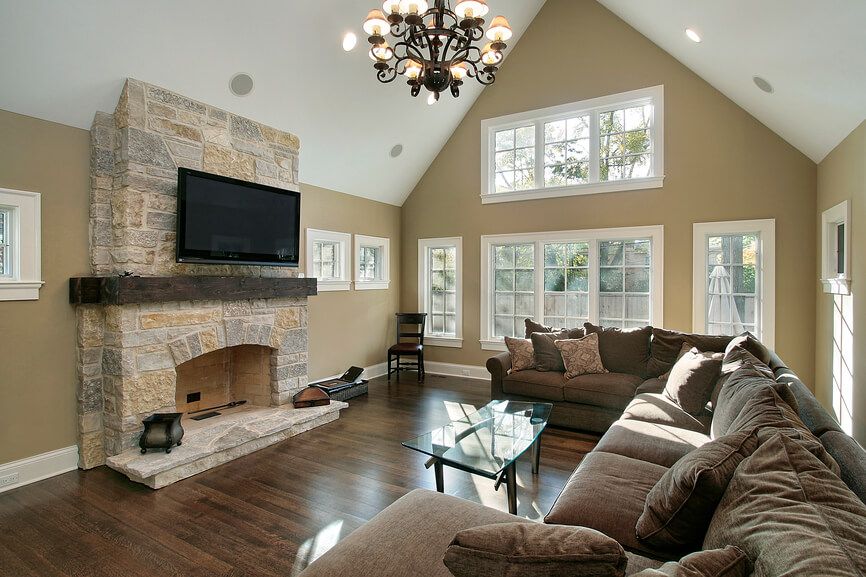 The perfect space for entertaining, this living room features an extra large comfortable sectional, stone fireplace, medium brown hardwood floors, and creamy tan walls. The soaring ceiling adds the illusion of extra space, and the plentiful windows brighten the entire space.