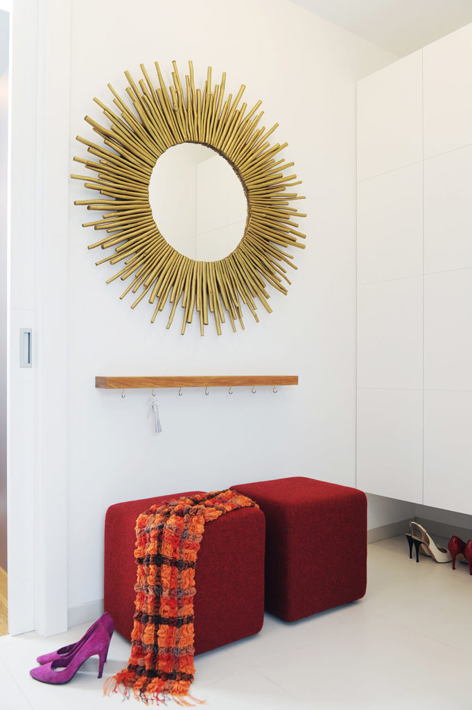 In this space, we see a pair of red cubic ottomans beneath a built-in key rack and sun-framed mirror. Sleek white storage panels at right flaunt their hardware-free appearance.