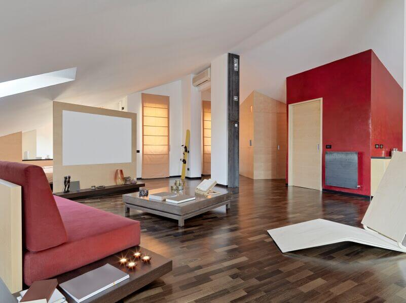 A beautiful open concept living room with multi-tonal wood floors and a rich red accent wall across from the seating arrangement. The bold red ties into to the modern wedge-back sofa.