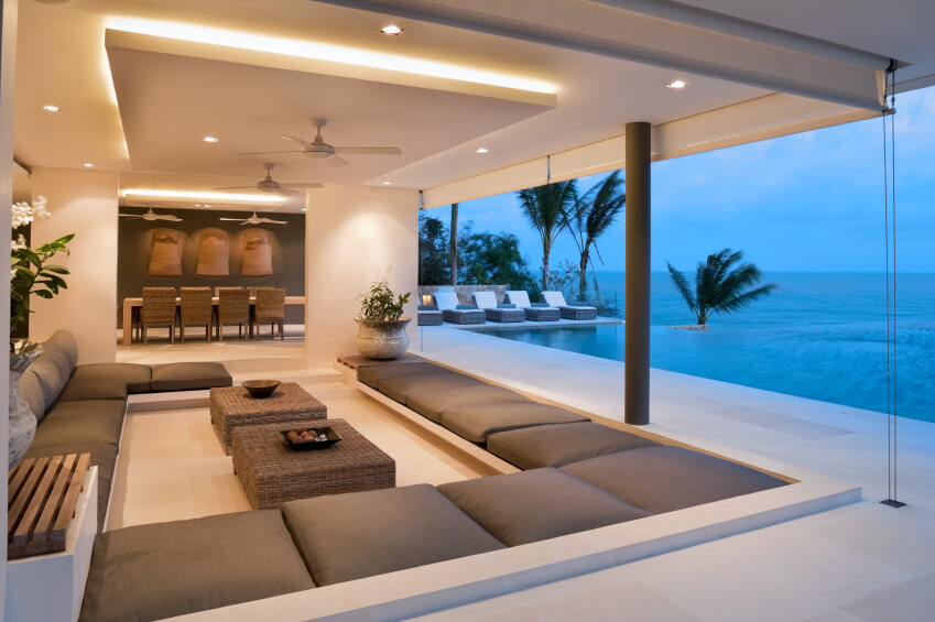 This stunning living area overlooks a crystal blue ocean. The seating area is comprised of light brown square cushions which surround two natural fiber coffee tables. A peek into the dining area reveals further earth tones, with both spaces complementing each other beautifully.