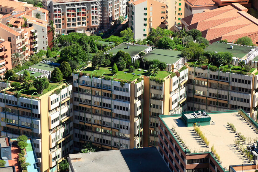 This modern apartment complex features an intricate, interconnected array of green roofs, with lawns and full trees sprouting from the top of the buildings. This creates a rooftop yard scenario, adding a breath of fresh rural air to the neighborhood.