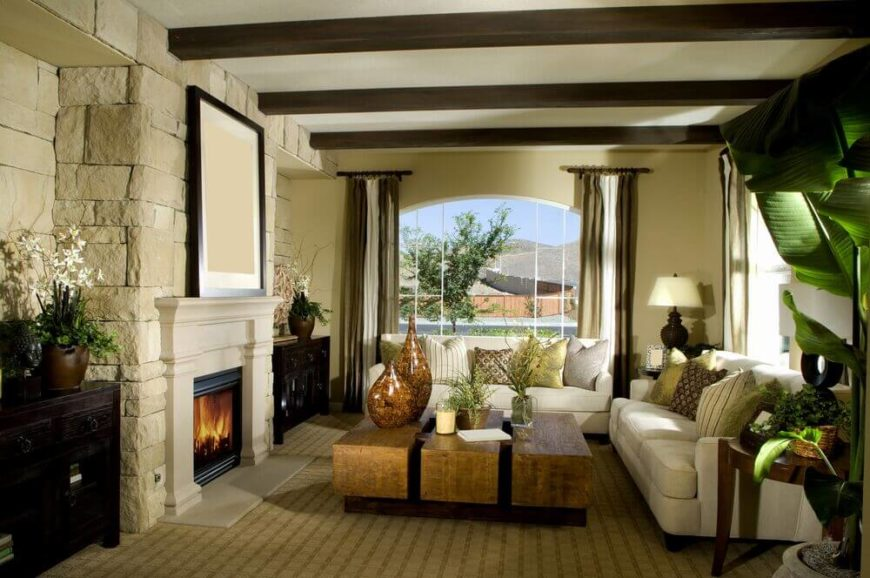 The stone fireplace expands into an entire stone accent wall, with two dark wood tables nestled in the nooks on either side of the fireplace. Exposed wooden beams across the ceiling add further elegance.