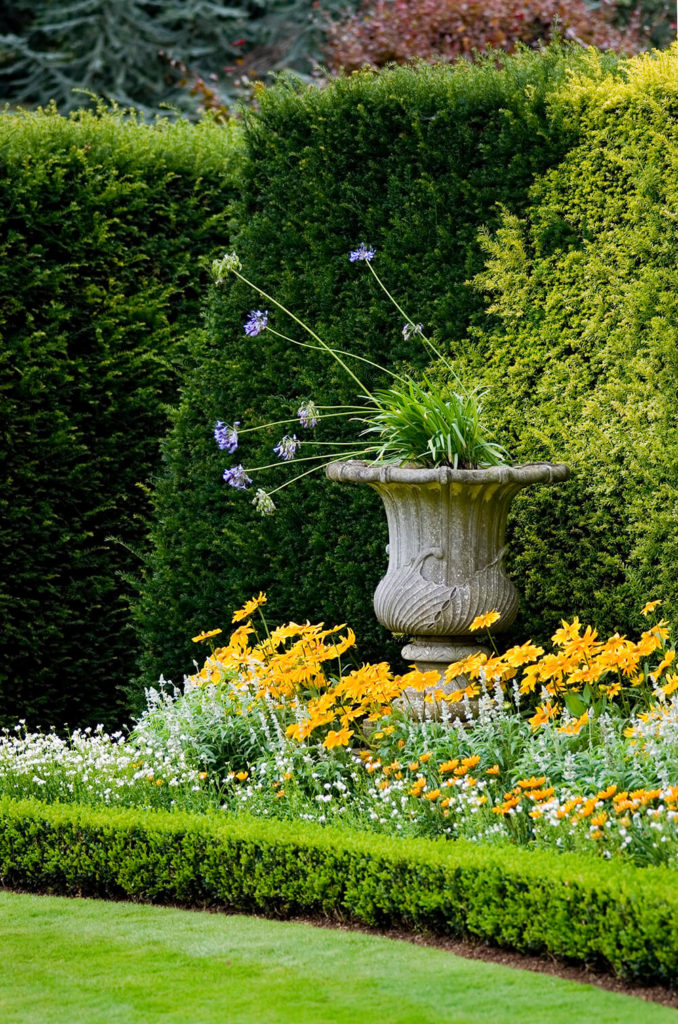 Layering different sizes and shapes of hedges attracts visual interest. The small hedge not only keeps the flowers in check, it also forms a clean line with the lawn making up keep easier.