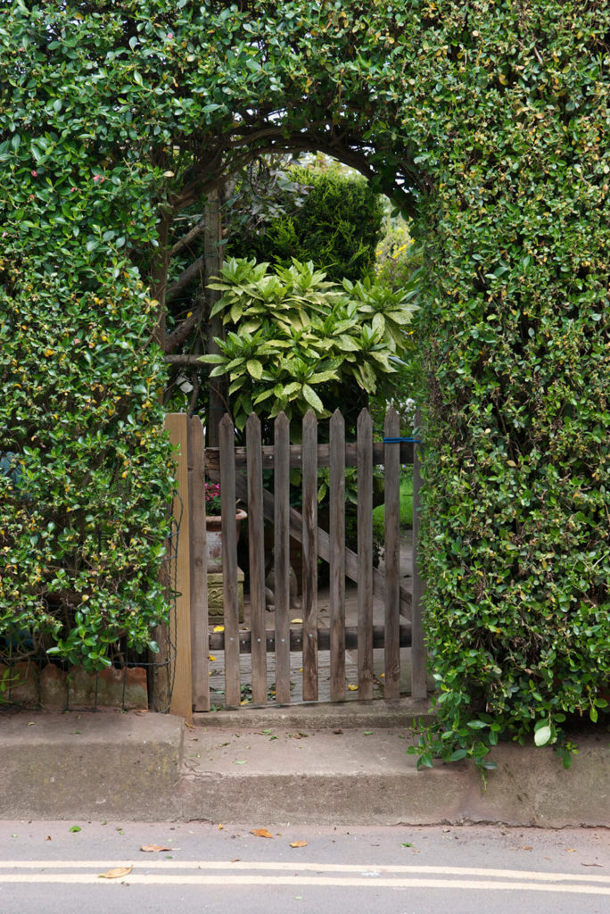 The whimsical entrance created by the arched hedge leads into a fitting garden. The quaint wooden gate is a nice added touch.