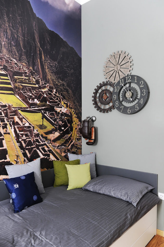 The guest bedroom boasts a daybed with hidden storage, standing beneath a set of gear-themed clocks and a large wall print of Machu Pichu.