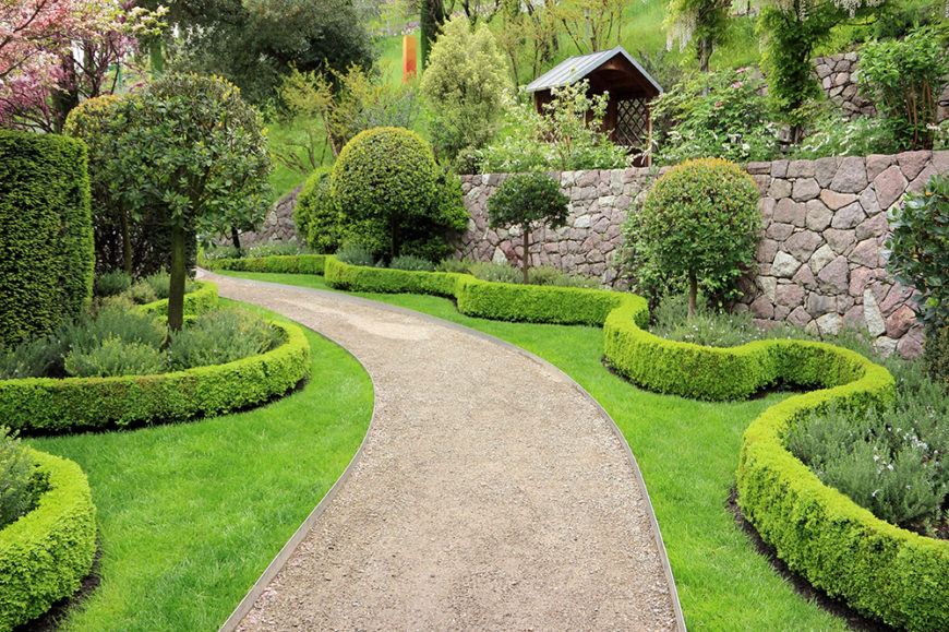 The waving lines of this hedge creates pockets of interest along this swooping pathway. Bordering something as structured as the stone wall in the background with something with lots of movement keeps a garden from becoming too stiff and uniform.