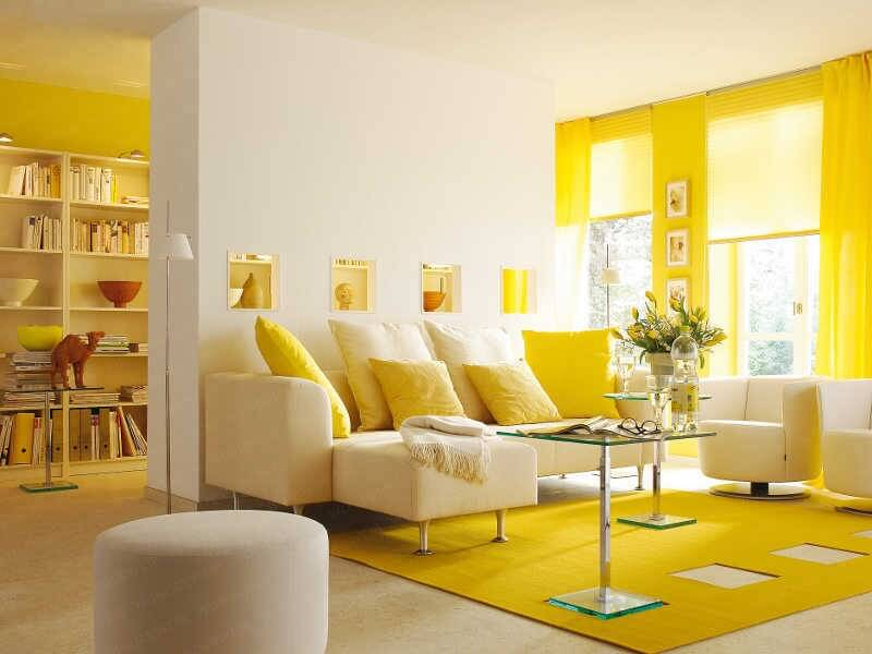This beautiful modern and minimalist living room is in pristine white and bright, sunny yellow. A half-wall with a series of passthroughs separates the seating area from a library and office area. The long wall to the right is a bold accent wall in sunshine yellow.