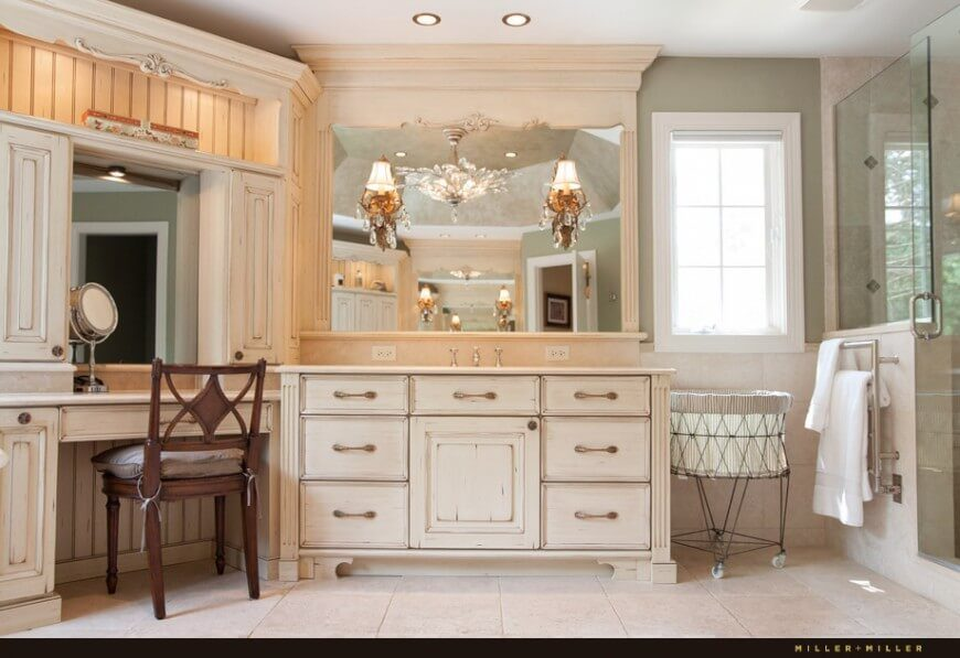 The same bathroom from a different angle exposes the quaint vanity and the rustic country textures on the wood. Elegant lights on the mirror create a classic atmosphere.