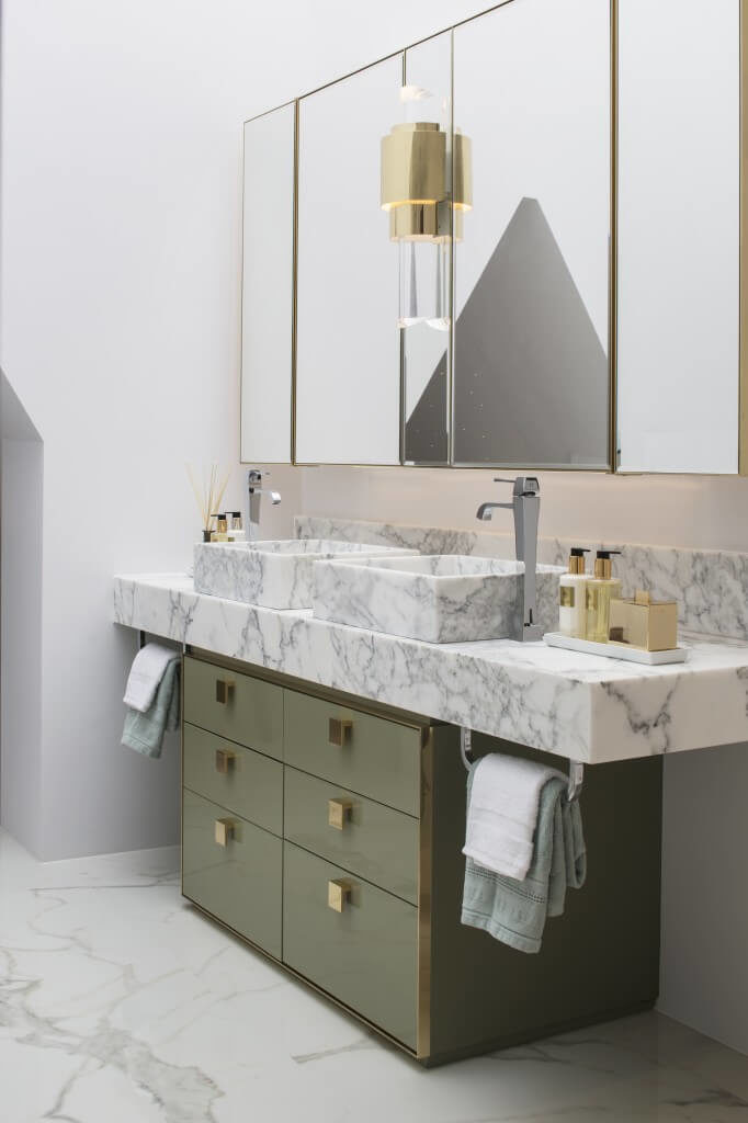 Another view of the bathroom focuses on the marble countertop of the vanity. The vessel sinks are also made of marble and the faucets come from either side of the sinks.