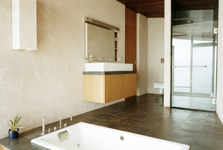 This very unique bathroom has a bathtub built directly into the floor and a square toilet. The vanity and vessel sink are square and floating up from the ground.