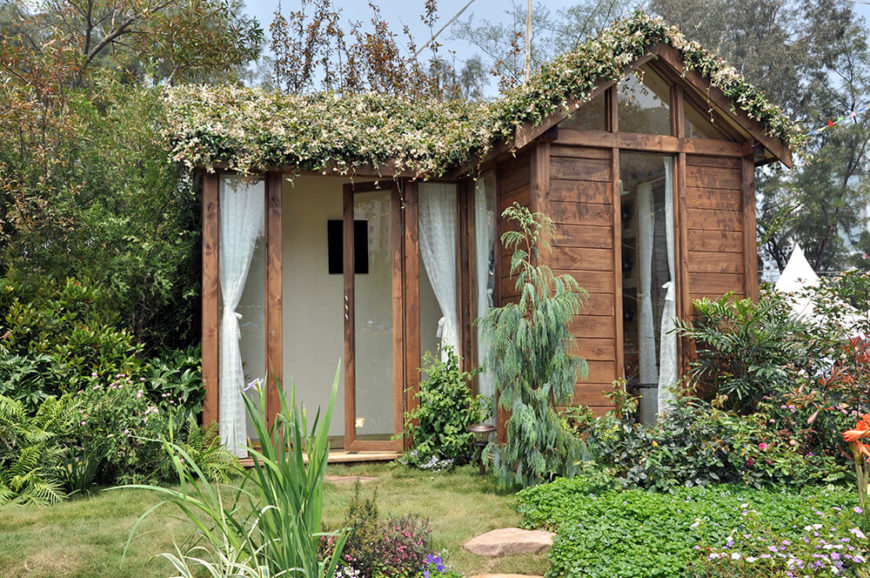 This small home features rustic textures over a modern look, with expansive glass panels and light natural wood exterior beneath a verdant living roof. The vine growth on the roof spills over the edges, helping to fully submerge the structure in nature.