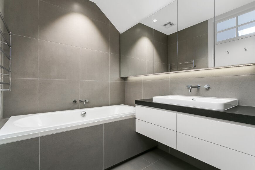 This minimalistic bathroom has a very calm and neutral color scheme. A large mirror move all the way across one wall and hovers over a floating vanity.
