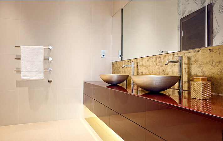 This unique bathroom features a light golden color scheme throughout the room. A soft amber glow comes from lighting under the floating vanity.