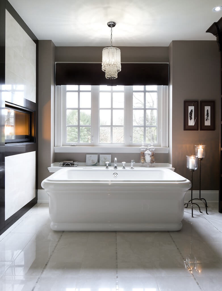 The same room has a very large bathtub with a shelving unit beside it for storage. A small crystal light fixture and candles give this room a very peaceful atmosphere.