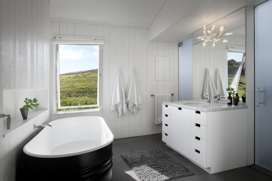 This cottage bathroom uses a lot of white colors for a bold contrast with the floor. A shelving unit is carved out of the wall for optimal storage.