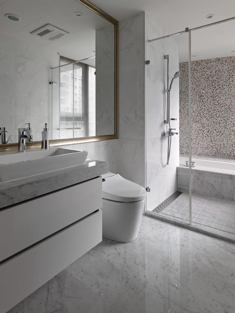The bathroom is wrapped in white marble from the floor on up, boasting both a glass enclosed walk-in shower and marble vanity with extra-wide vessel sink.