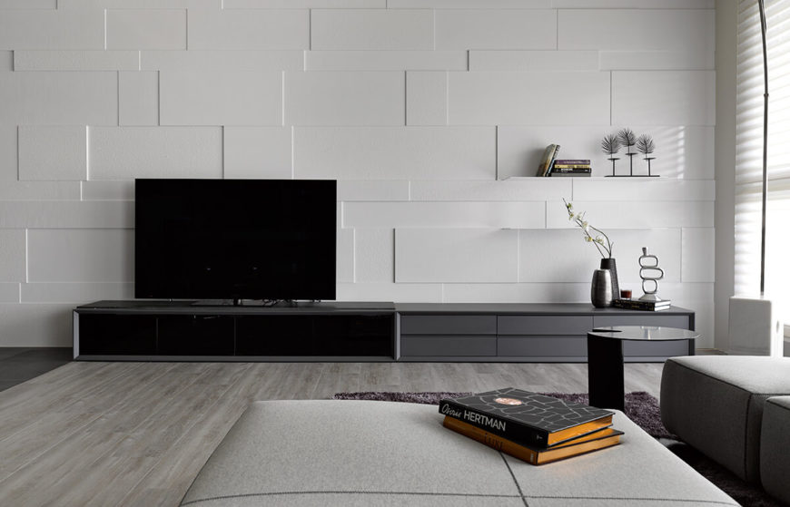 With this close look at the white wall behind the entertainment center, we can appreciate the angular, geometric textures, adding nuanced detail to the white space. A couple shelves are discreetly built into the wall.