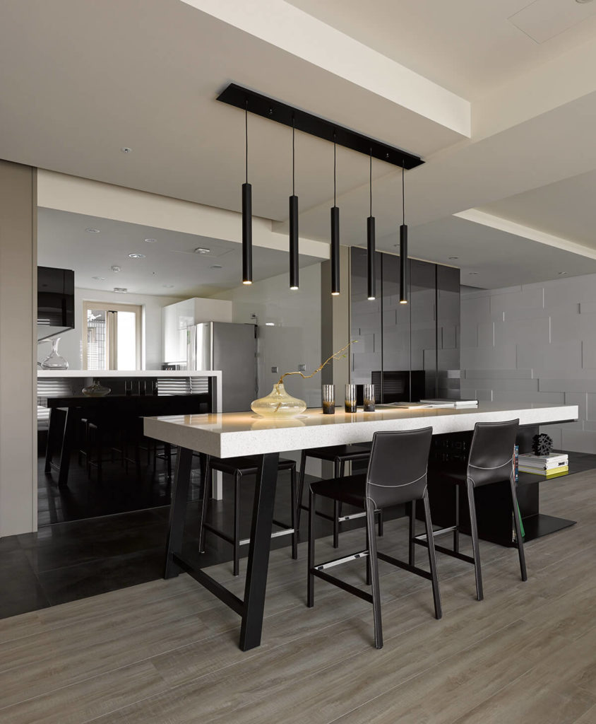 The island features a thick slab marble top and dark wood body, surrounded by contemporary leather upholstered bar stools. The kitchen can be seen beyond, clad in glossy white textures from top to bottom.