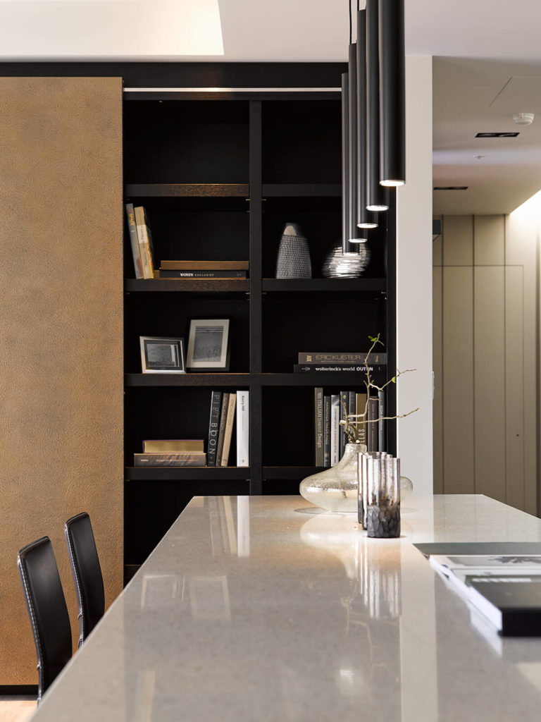 Glancing down the reflective surface of the island, we can get a close view of the built-in bookshelves, flush in dark stained wood for a high contrast appearance in the home.