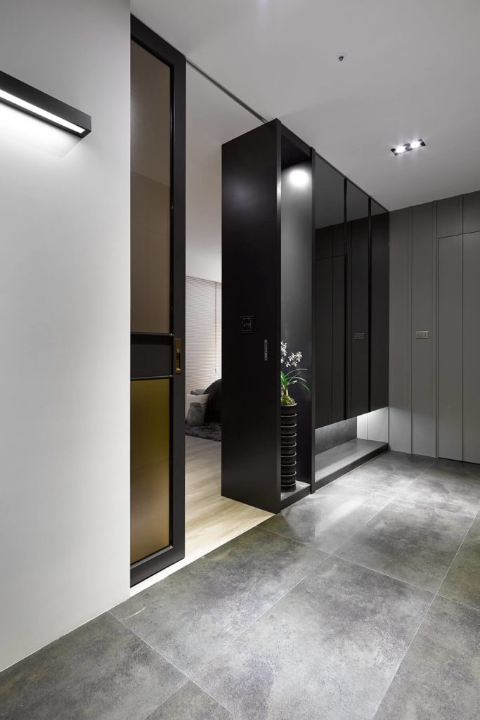 The entrance to the primary bedroom sports another pocket door, and is framed by a glossy black wall with inner-lit display shelving.
