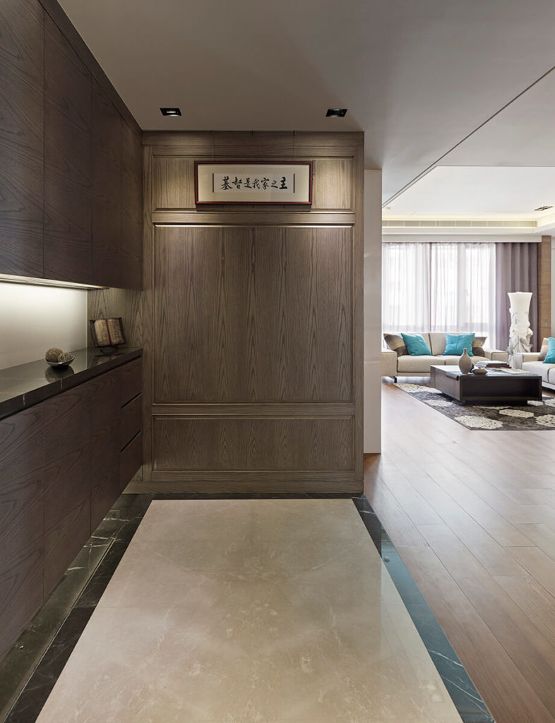 In the entryway, a slim marble floor segment highlights the bespoke arrangement of dark wood and sleek paneling.